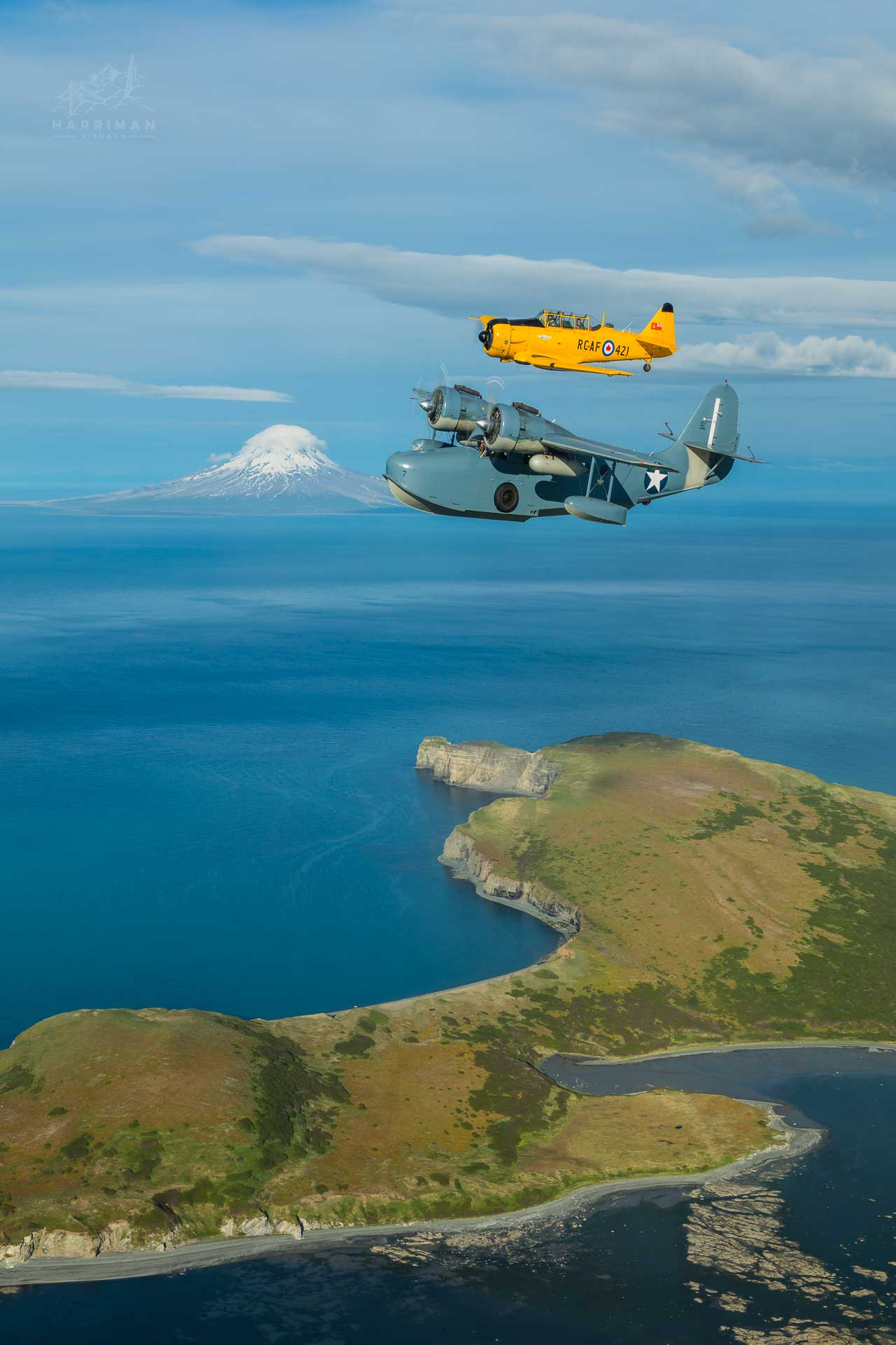 Canadian Harvard Mk IV and a JRF-5 Grumman Goose flying by Augustine Volcano, Alaska